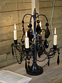 Burning candles in a candle holder decorated with black beads
