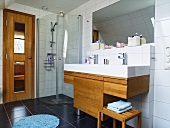 A tailored made washstand with a wooden cupboard underneath and a glass shower cubicle next to it