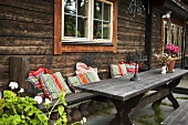 Rustic wooden patio table with colorful pillows in from of a wooden facade with windows