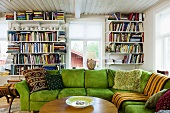 A living room with a green corner sofa in front of a book shelf