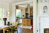 A dining area and an old tiled stove in front of an open-plan kitchen with a view of a counter