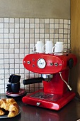 A red espresso machine with coffee cups and a croissant on a plate in the corner of a kitchen with white mosaic tiles