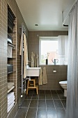 Brown mosaic tile in a bathroom and built in niche with hand towels and view of the sink at the window
