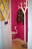 Open front door with a view of a white coat rack and pink foyer walls