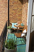 A sunny spot on a balcony in front of a brick facade with wooden chairs and pots of lavender