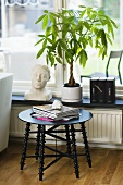 Black side table in front of a window seat with houseplants and a bust