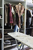 An open wardrobe, hangers and an ironing board in a dressing room