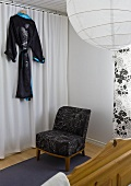 A corner of a bedroom - a chair in front of a curtain and a black kimono hanging up