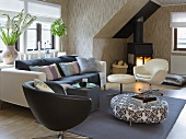 Club chairs, a sofa, a pouffe and a fireplace in a living room