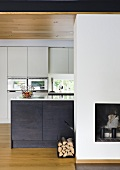 A kitchen counter with black cupboards in front of a white built-in cupboard and a fireplace