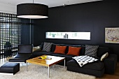 A black wall with a narrow window and a wooden lattice wall in a living room furnished with black chairs and a sofa and a wooden coffee table