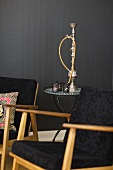 A black 1950s armchair with an occasional table and a water pipe against a black wall
