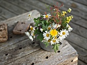 A bunch of meadow flowers in a metal pot on an old wooden shelf
