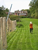 Fishing nets hanging in a garden with a woman and view of a wooden house
