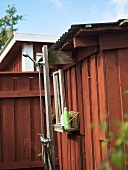 A homemade outdoor shower on a red-painted wooden house