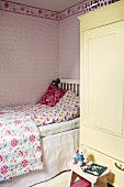 A child's bedroom with a bed, a cupboard and pink floral wallpaper on the wall