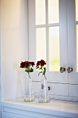 Two vases with red flowers on the shelf on a white kitchen cupboard with opaque glass doors