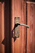 An old red, wooden door with a handmade metal handle