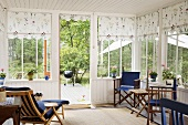 Wooden chairs in a conservatory with white wooden panelling and floral fabric blinds at the windows