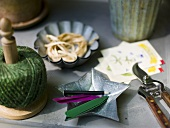 A roll of twine and a bowl with pencil and craft untensils on a table