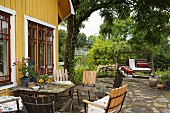 Garden furniture and a swinging chair on a natural stone patio in front of a yellow wooden wooden house