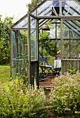 Gewächshäuschen in Holzglaskonstruktion und Garten mit blühenden Wiesenblumen