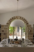 Table set for a party in front of a window a tiled round arch
