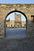 View through an old stone archway of an Italian piazza and historic buildings
