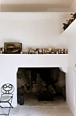 Fireplace with a collection of silver cups on a mantel and a metal chair