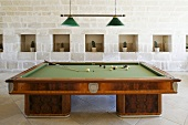 Billiard table in a hall in front of stone wall with cactus in the wall niches