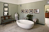 Free standing bath tub in front of a gray wall on a stone floor and antique bench