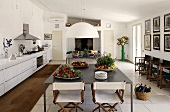 Kitchen with eating area -- plates with vegetables on a gray metal table and folding wooden chairs with white upholstery on a white tile floor