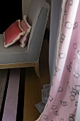 Pillows on a gray armchair in front of a pink curtain