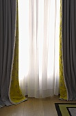 Window with gray and white floor length curtains