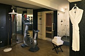 Gym equipment in front of mirrored closet doors and sauna with glass shower doors