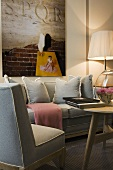 Gray upholstered sofa set with cushions in front of a wall with a picture and floor lamp
