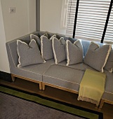 Light gray sofa and pillows covered in the same material in a bay window in front of closed blinds