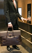 Person with a briefcase pushing the buttons in an elevator