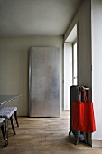 Simple closet and red bag hanging on a radiator in a minimalist dining area