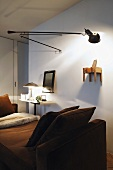 Lounger in front of a room divider with adjustable wall lamp