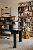 Black table in front of a illuminated book shelves in a wall niche and wall shelving in 50's style