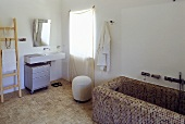 Country style bathroom -- bathtub with brown mosaic tiles and washstand with a mirror by the window