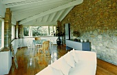 White sofa and dining area under a beam ceiling and natural stone wall in the living room of a country home