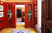 Elegant lobby with red paneled walls and flowers in niches with a view into a living room