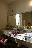 Dimly illuminated marble vanity with bathing items and a wall mirror