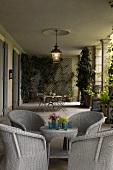 Hellgraue Korbmöbel und Pflanzenkübel in Loggia einer Villa mit Laterne an der Decke