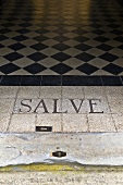 Latin greeting chiseled in stone and a floor with a checkerboard pattern