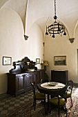 Vaulted ceiling with a wrought iron chandelier above a table and antique chairs