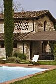 Liegestuhl am Pool vor südländischem Haus und überdachter Terrasse