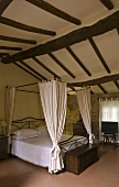 Bedroom under the roof - elegant canopy bed under a rustic beam ceiling